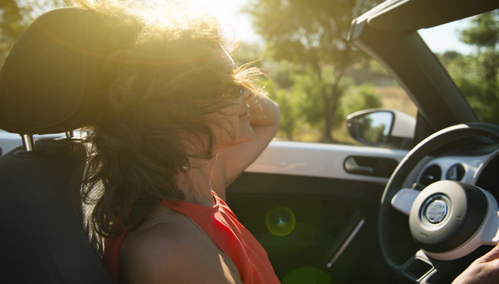 Woman Driving Convertible Car with Top Down