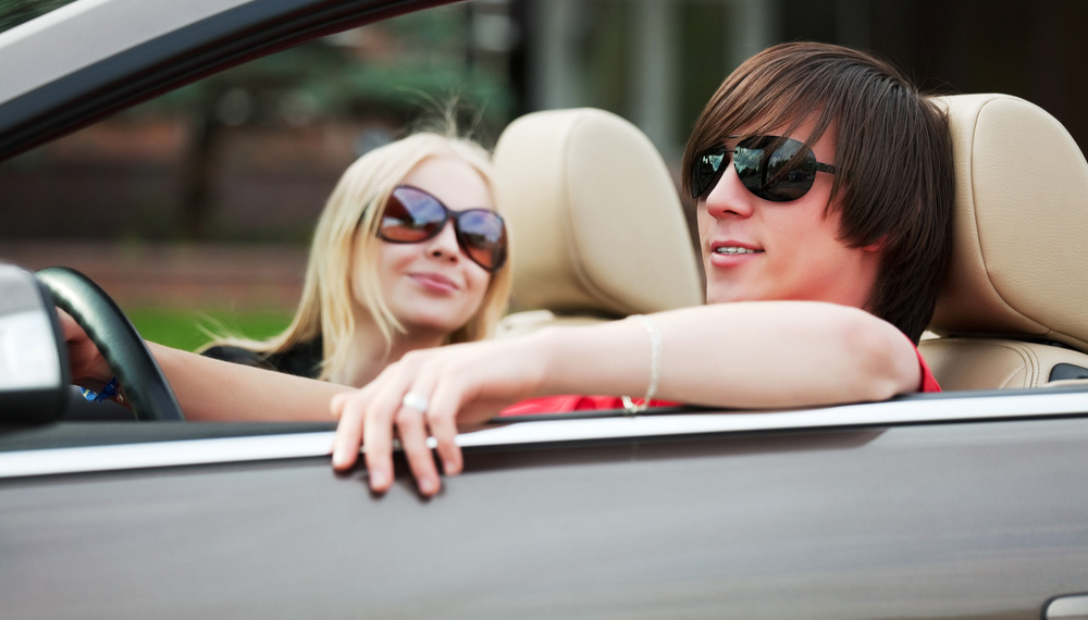 Young Couple Driving Convertible with Top Down